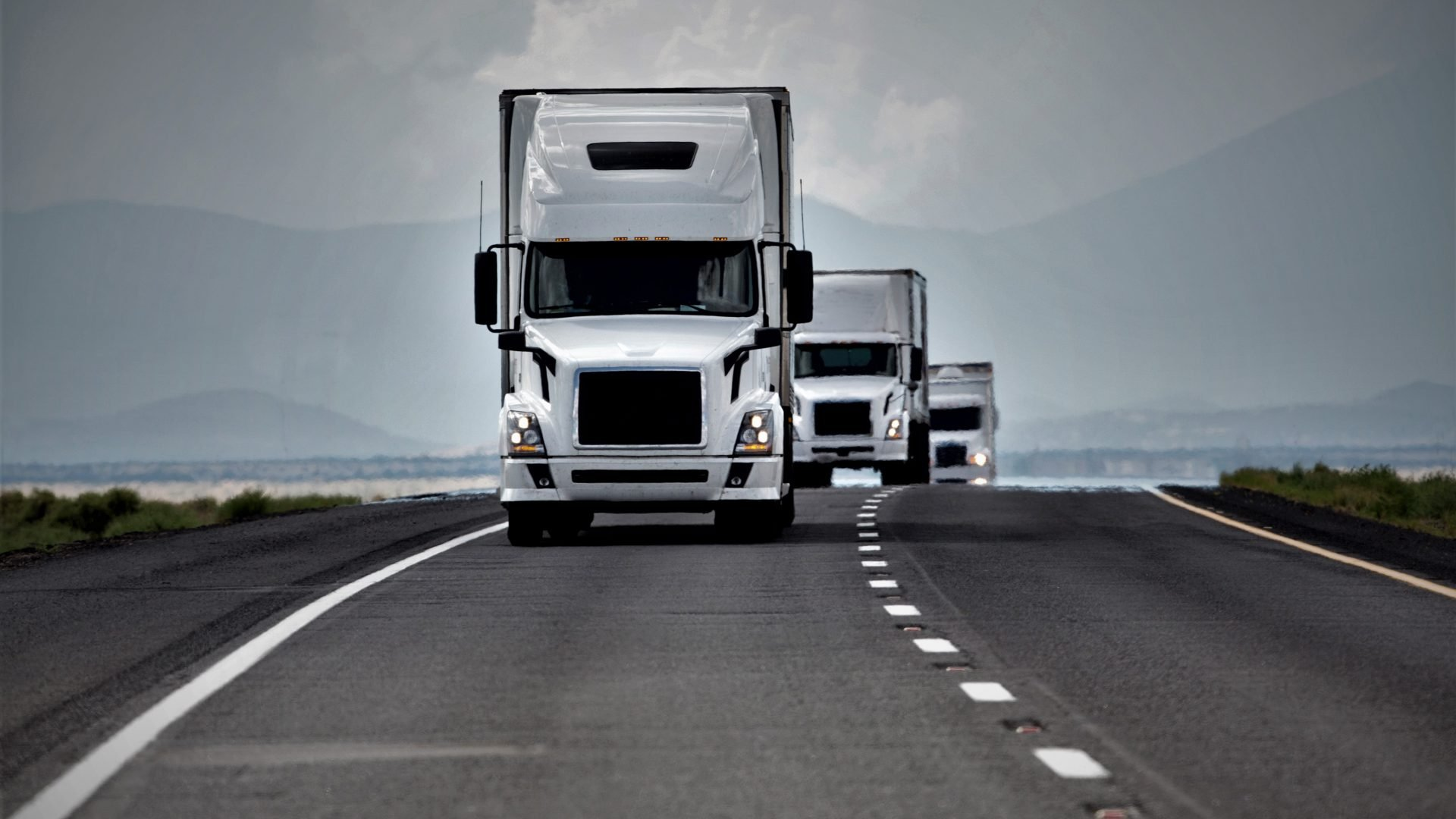 Three white trucks in a convoy on an interstate highway